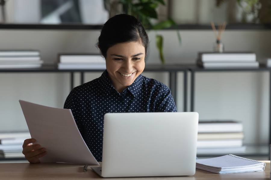 Woman holding paper and smiling at laptop