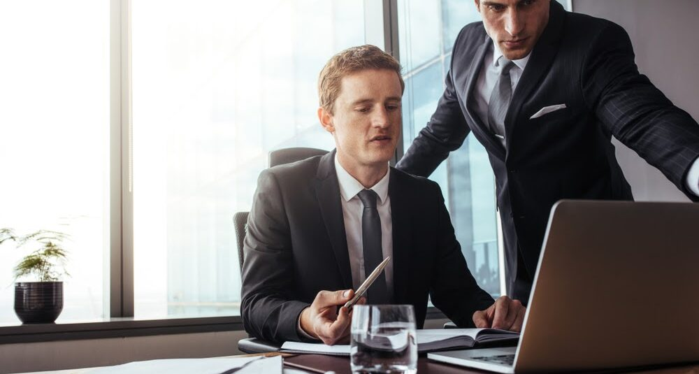 lawyers discussing law firm efficiency in front of a computer