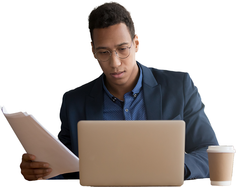 Man working on a laptop while looking at paper documents